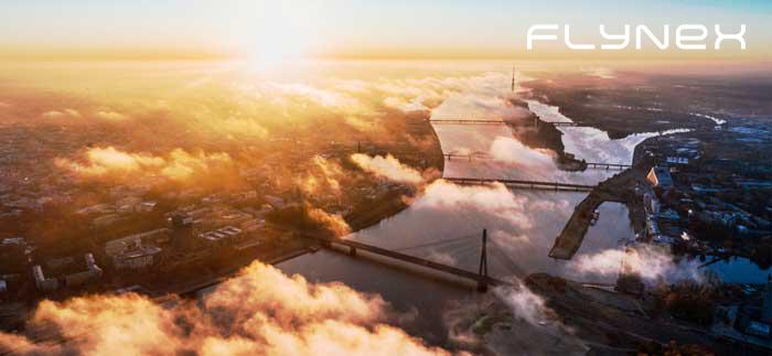 Drohnenbild über Fluss mit Brücke mit Wolken