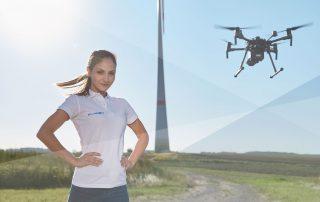 Frau mit Drohne vor einer Windkraftanlage